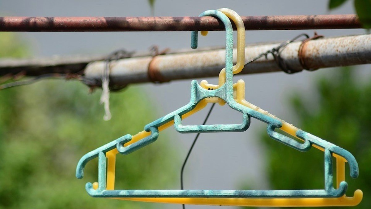 Two worn hangers hang outdoors.