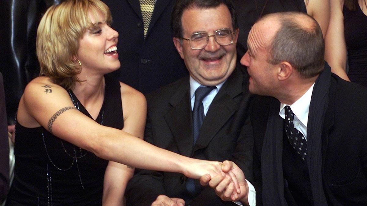 Melanie C från Spice Girls skakar hand med Phil Collins under uppsikt av italienska politikern Romano Prodi.