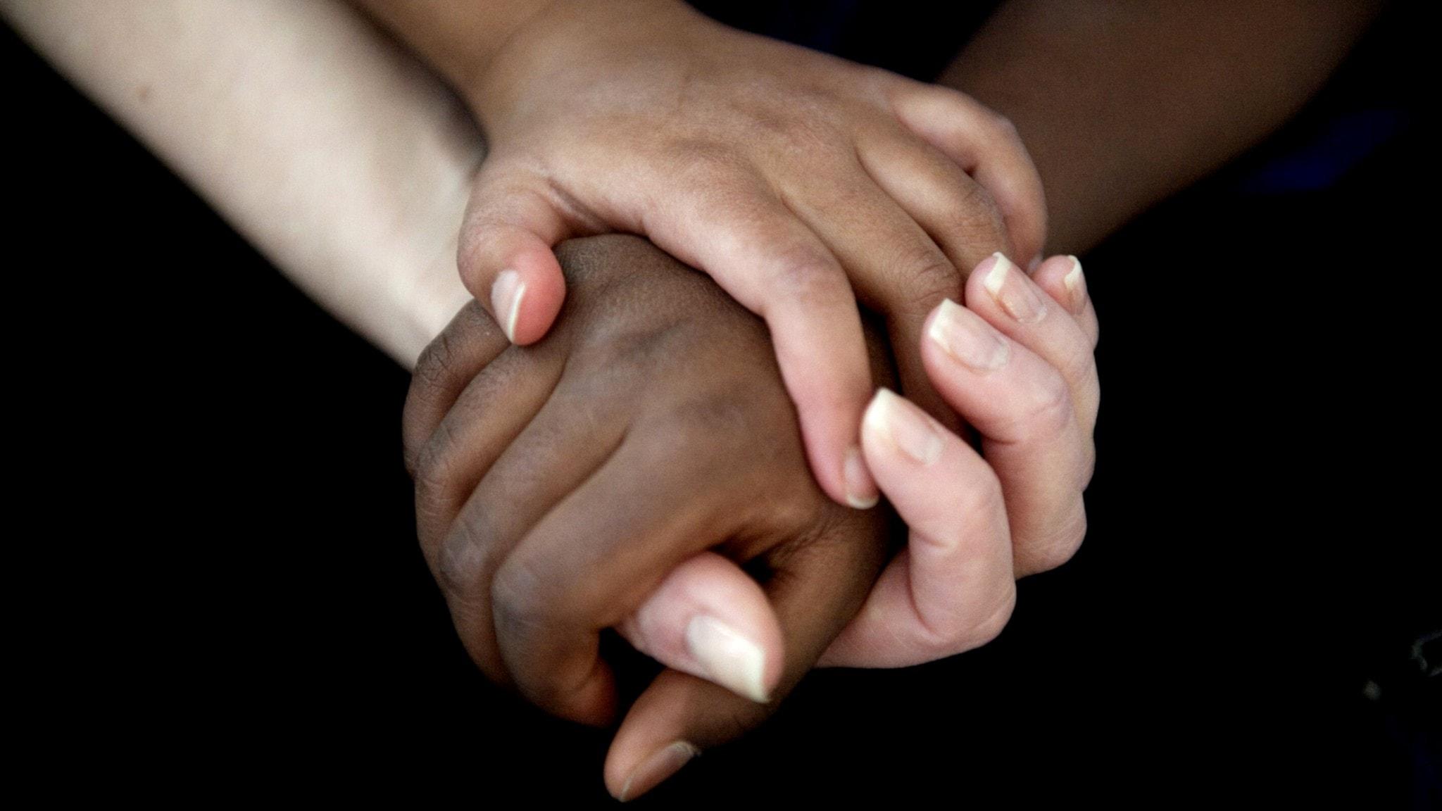 Tre händer håller om varandra.