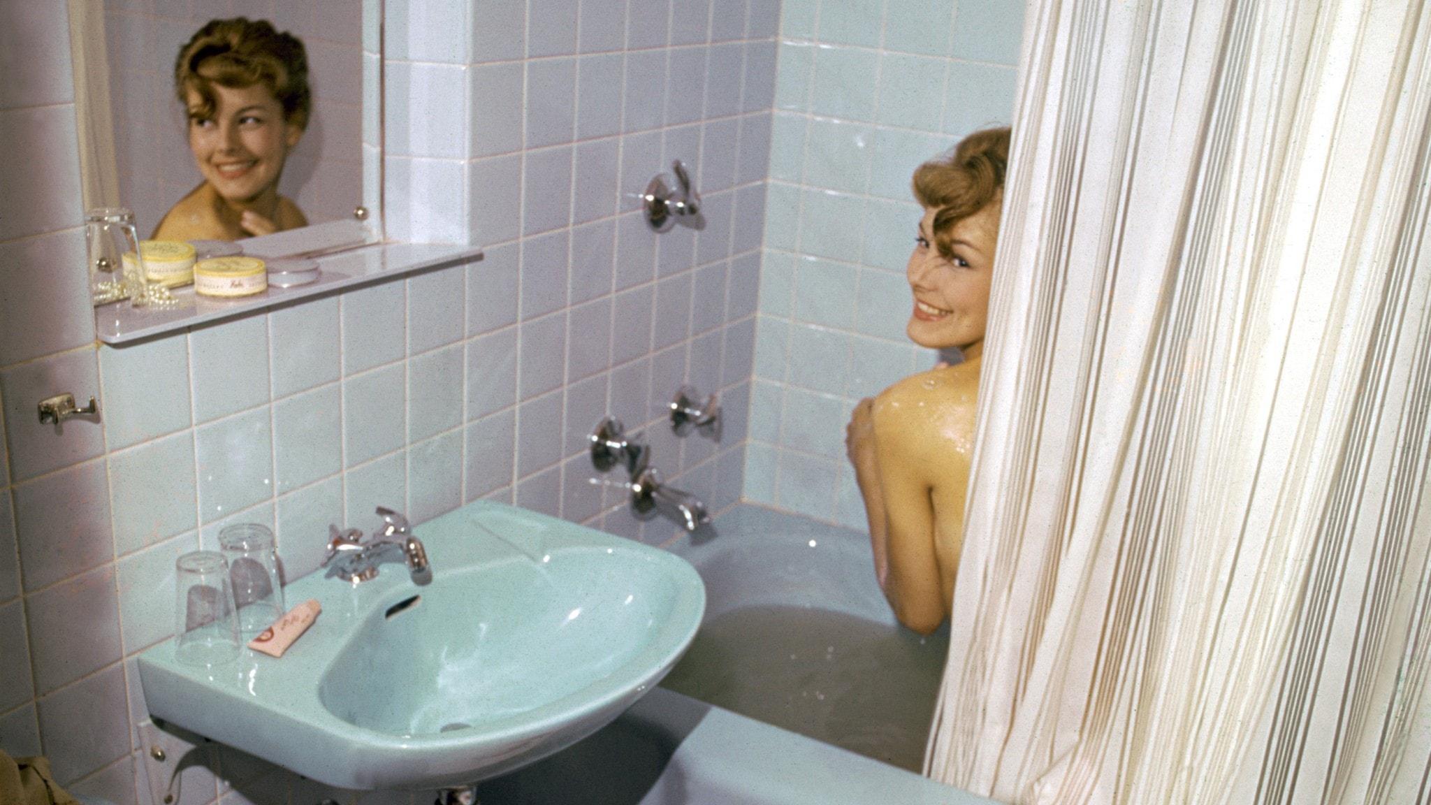 En kvinna kickar fram bakom en duschgardin i ett 1960-tals badrum med blått kakel och matchande badkar och handfat.