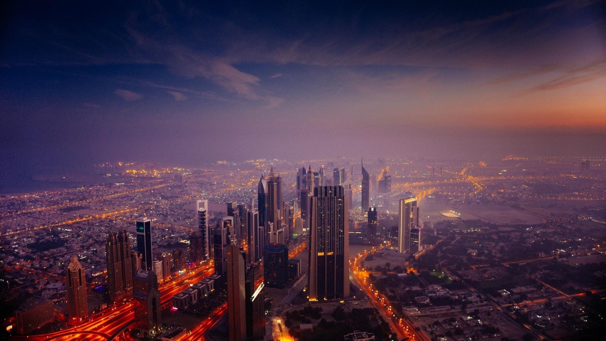 Gryning i Dubai, himlen är rosa och vi ser staden lite från ovan och en rad skyskrapor.