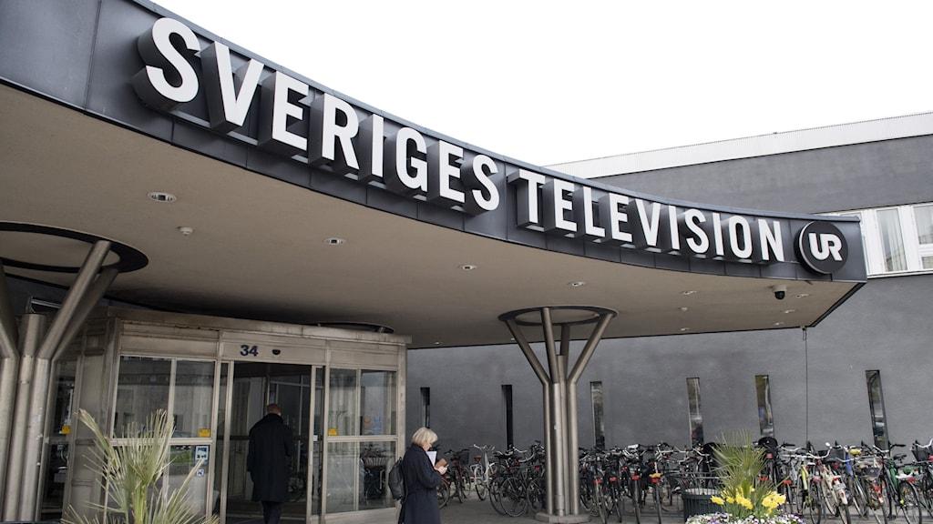 entrén till Sveriges Television. Det står Sveriges Television över en entré till en grå byggnad.