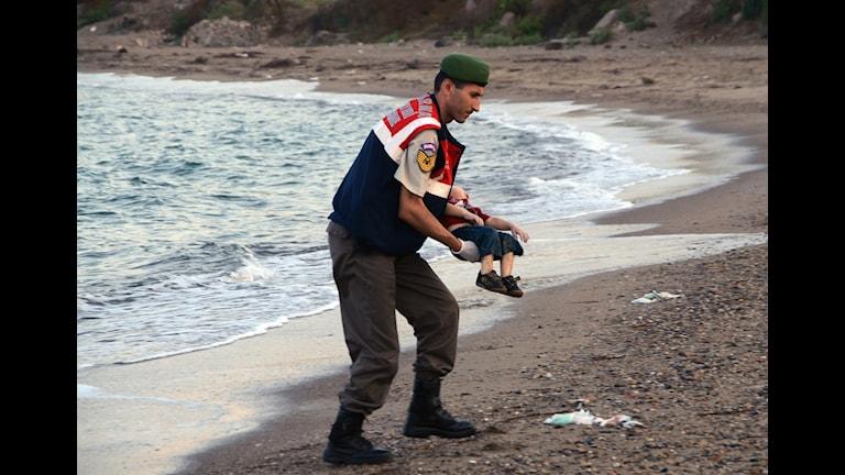 Alan Kurdi bärs bort på stranden. Foto: Nilüfer Demir/TT
