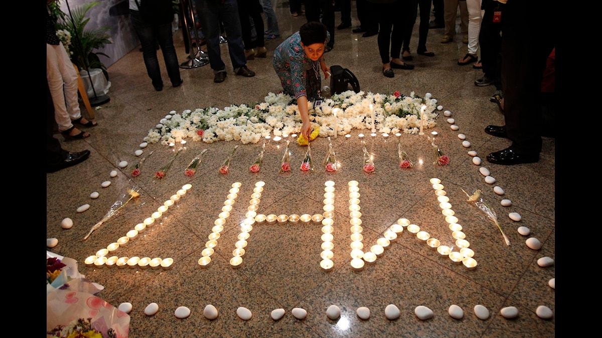 Tända ljus för passagerarna på MH17. Foto: Lai Seng Sin/TT NYHETSBYRÅN