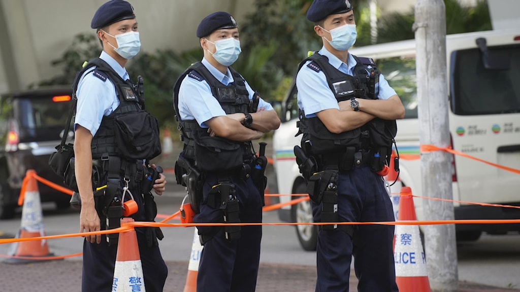 """Police officers stand guard outside local court in Hong Kong Thursday, July 22, 2021. Hong Kong police charged two top editors and two editorial writers at Apple Daily with collusion weeks after the city's largest pro-democracy newspaper was forced to cease publication and its assets were frozen. All four were charged with conspiring to """"collude with a foreign country or with external elements to endanger national security"""" under the city's year-old national security law and appeared in court Thursday. (AP Photo/Vincent Yu)  HK103"""