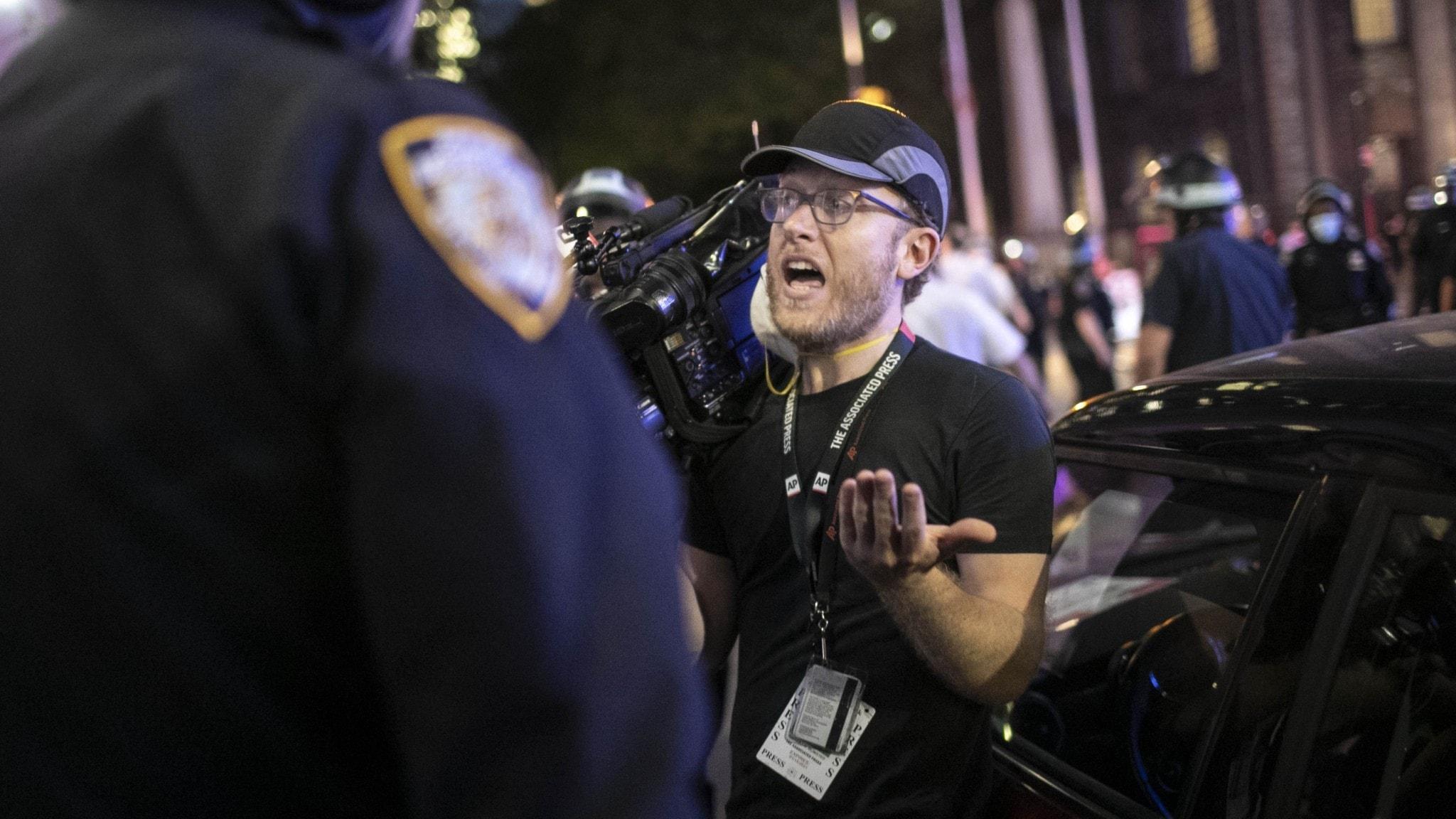 Journalist argumenterar med polis vid bevakning av protesterna i USA.