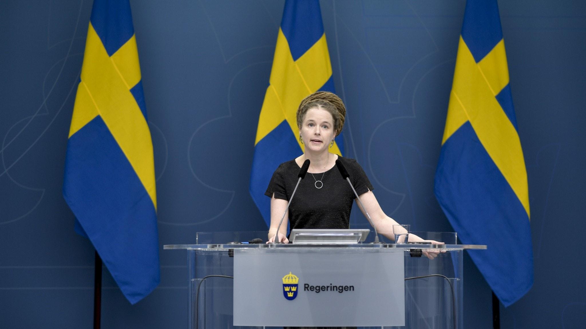 Kulturminister Amanda Lind framför tre svenska flaggor.