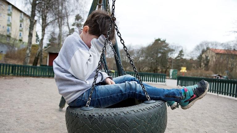 Ledset barn på gunga