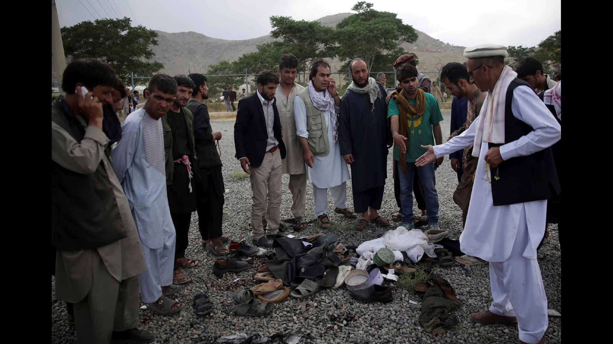 Männen försöker identifiera offren efter terrordådet mot den begravning i Kabul där den unga mannen enligt Blankspots uppgifter skulle ha dödats.