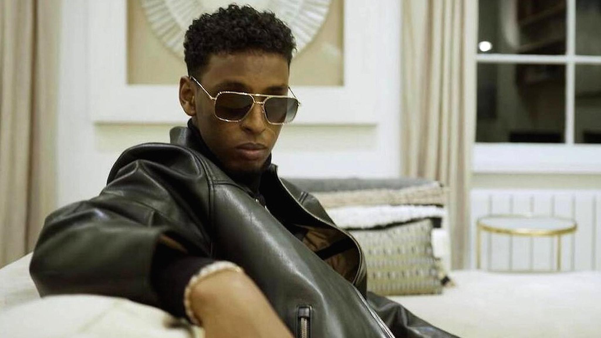 Rapparen Yasin sitter i en soffa med solglasögon.