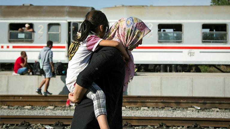 En kvinna bär sitt barn på tågstationen Beli Manastir, nära ungerska gränsen i Kroatien. Foto: AP Photo/Darko Bandic/TT.