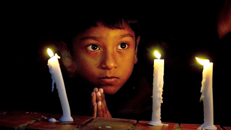 Ett barn tänder ljus i en kyrka i Islamabad, Pakistan. Foto: Anjum Naveed/TT
