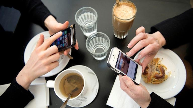 Två personer fikar och använder sina mobiler.