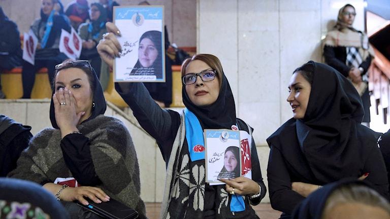 En iransk kvinna håller upp bild på kandidaten Parvaneh Salahshouri.