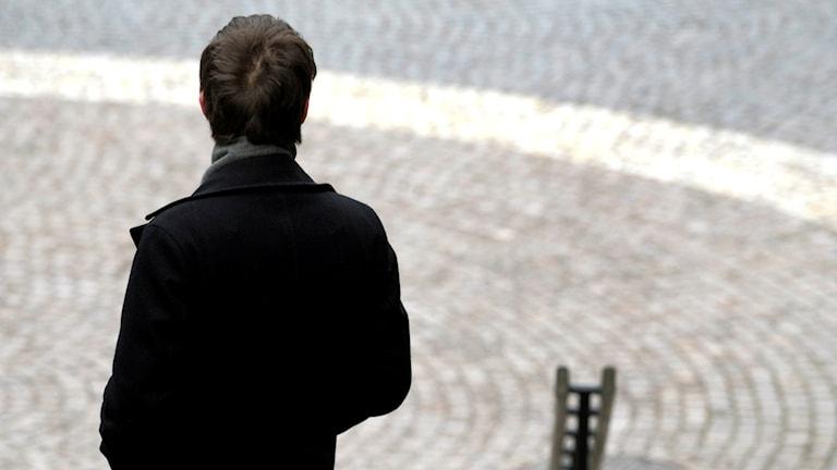 En man står med ryggen mot kameran.