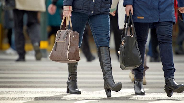 Kvinnor med handväskor på ett övergångsställe.