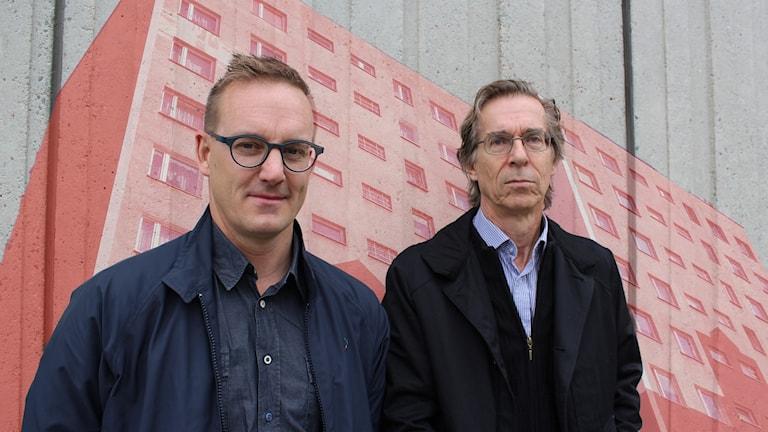 Fredrik B Nilsson och Hans Lind står vid en betongvägg med en röd husskiss i bakgrunden.