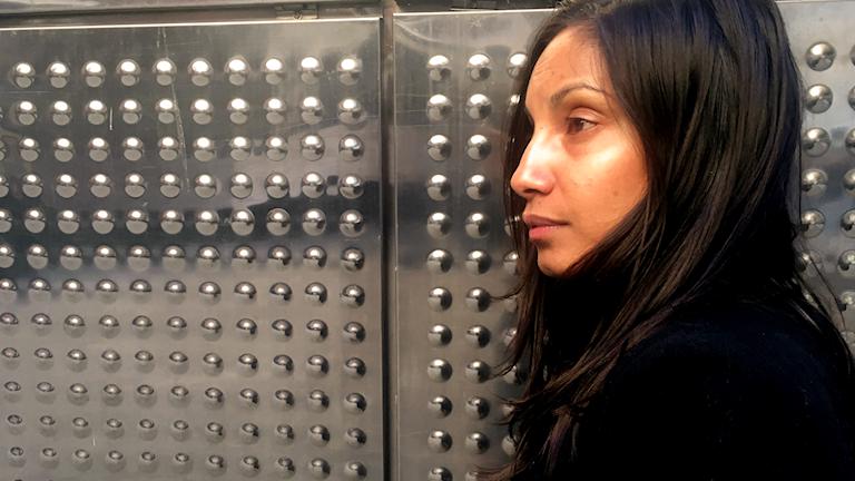 Maria står i profil mot en vägg i metall.
