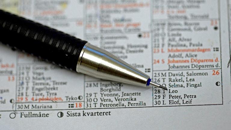 En penna ligger på en almanacka där man kan läsa namnsdagarna