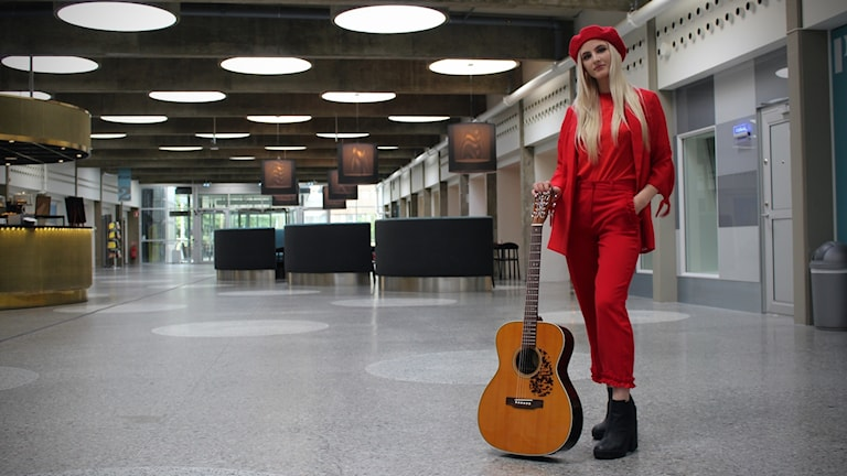 Nova Miller står i Radiohusets hangar med en gitarr vid sin sida.