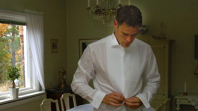 En man funderar under tiden han knäpper skjortan.
