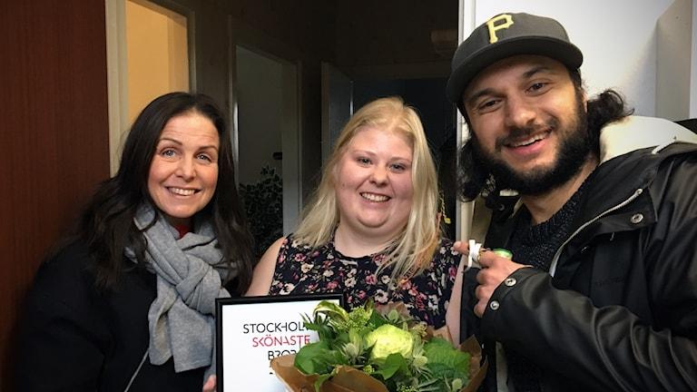"""Titti Schultz och Farzad Nouri gratulerar Emelie """"Semlan"""" Söderstrand med blommor och diplom."""