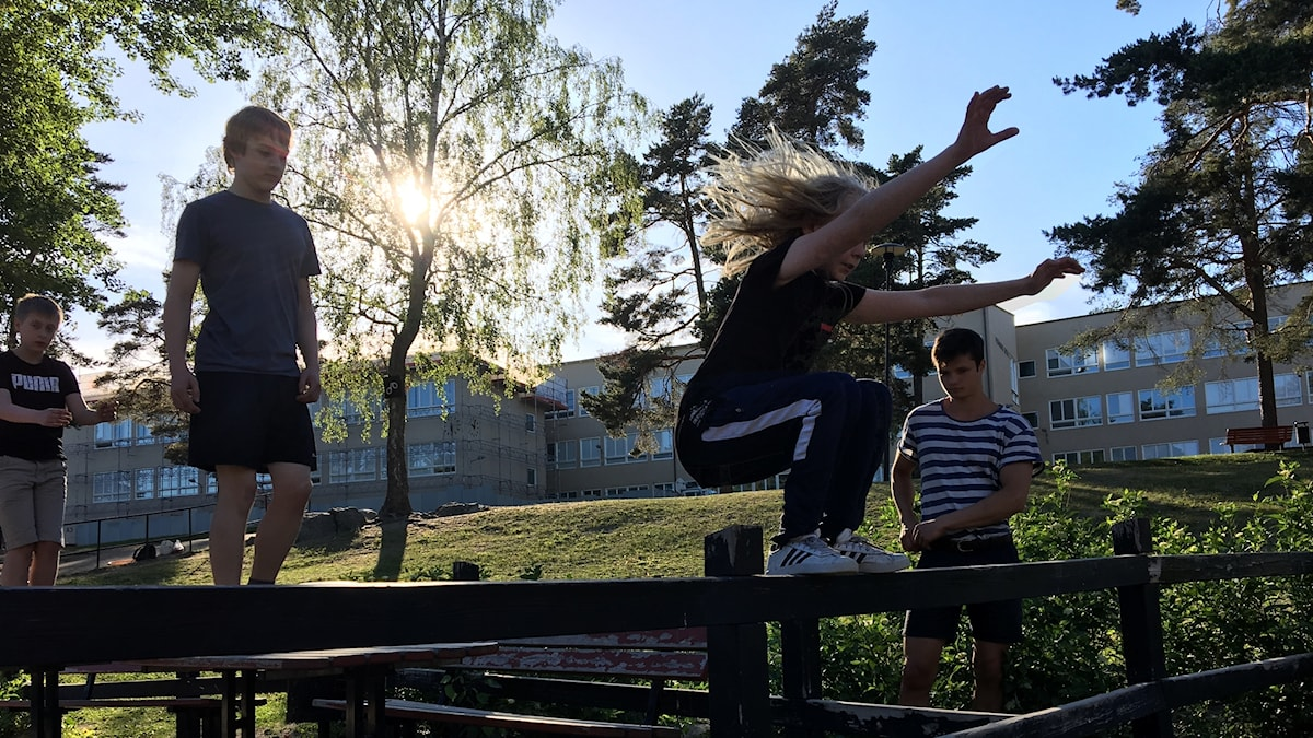 Barn balanserar på ett räcke under en parkourträning.