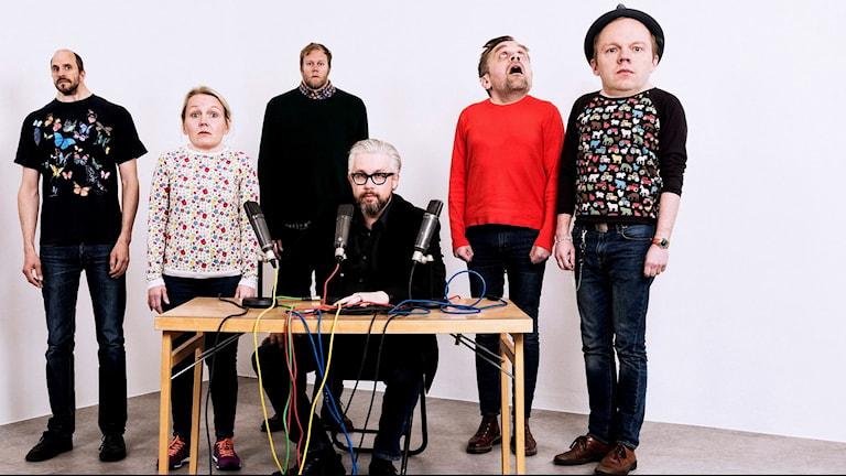 Humorprogrammet Mammas Nya Kille i ett vitt rum. De är sex personer, en kvinna och fem män. Alla har fått sina huvuden antingen komiskt förstorade eller komiskt förminskade. I mitten sitter Bengt Strömbro vi ett sändningsbord och tittar in i kameran.