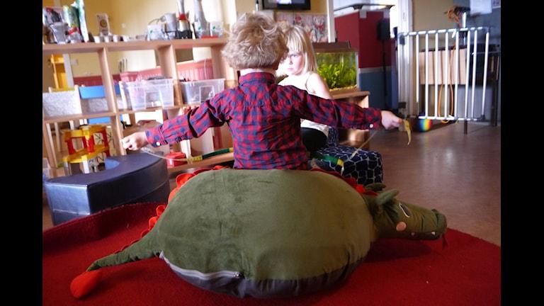 Olle och Ellen sitter på drakkudden inne på förskolan. Fotograf: Henrik Kemppainen/UR