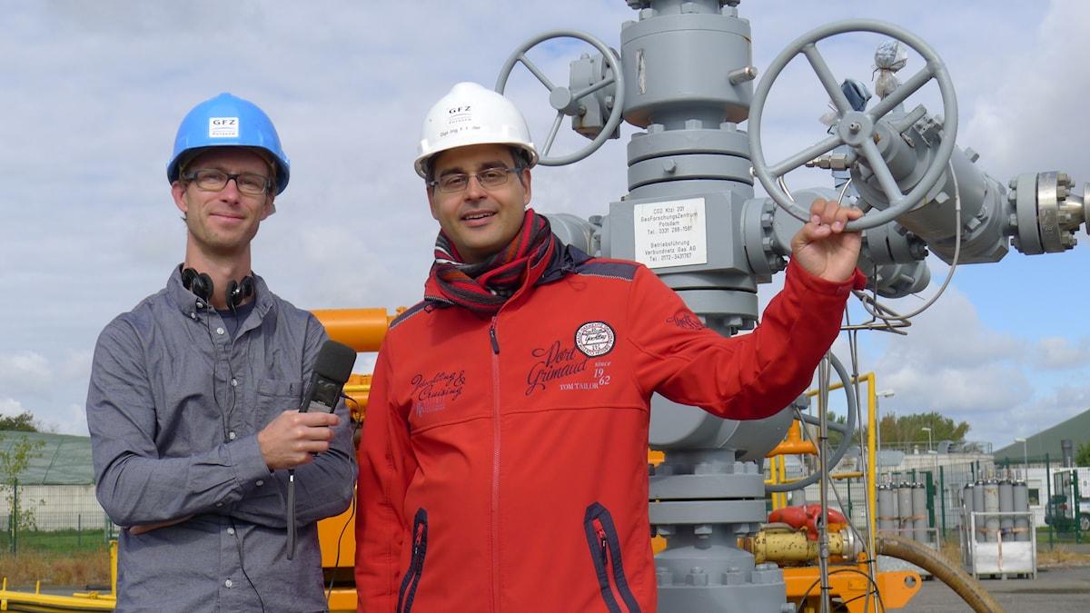 Klotets reporter Björn Gunér står med Fabian Möller ifrån det tyska geologiska forskningsinstitutet, GFZ,  vid brunnslocket till det koldioxidlager som studerats i Ketzin utanför Berlin. Foto: Sveriges Radio