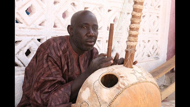 Alagi M'Bye med Koran, en kalebass med 21 strängar och spelas med tummar och pekfingrar.