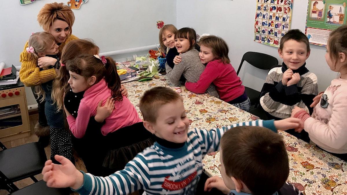 """Barnen i Kulturhuset i Marinka leker """"Krama din granne"""" med sin lärare Ludmila."""
