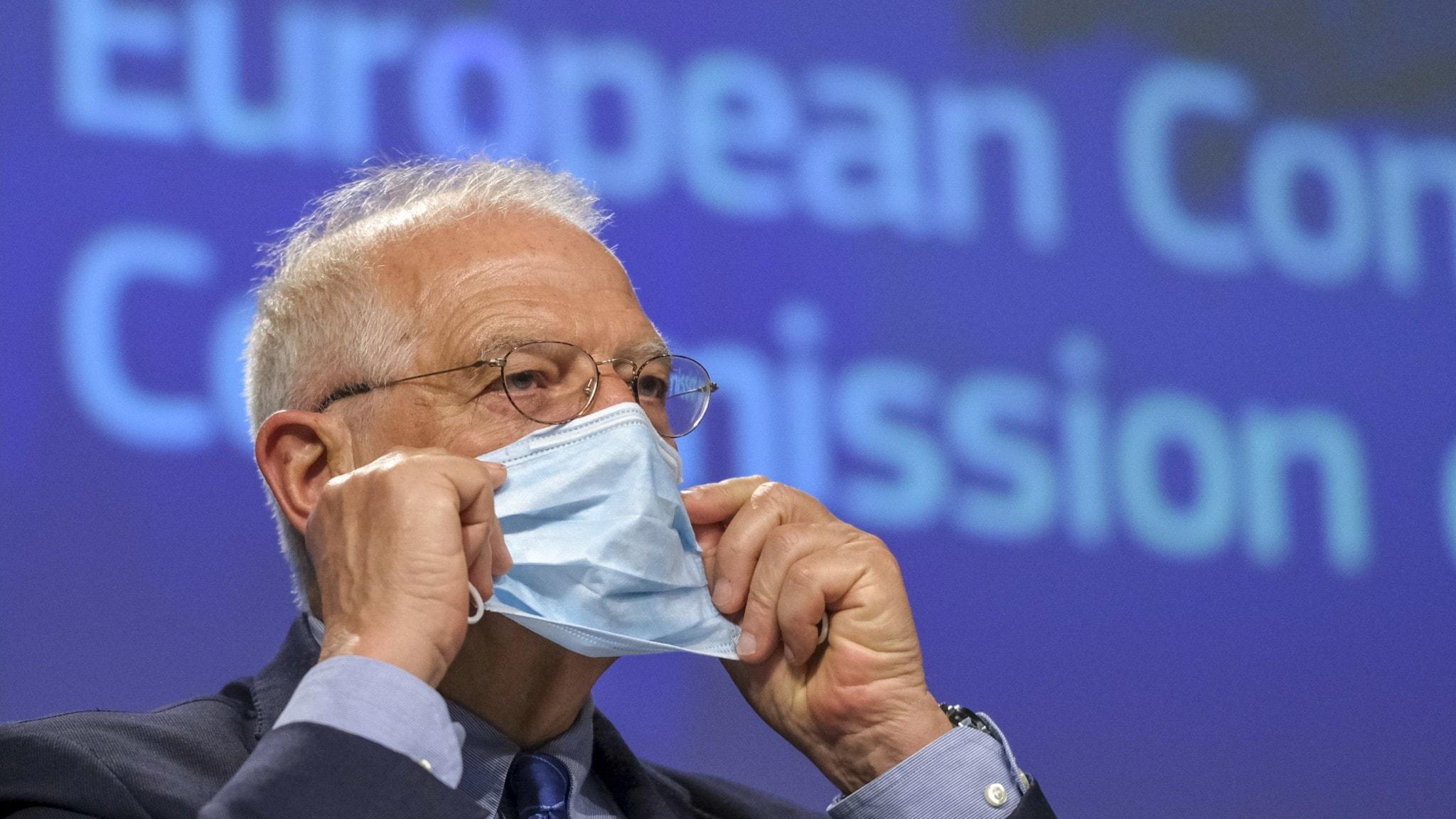EU:s utrikeschef Josep Borrell tar på sig skyddsmask under en pressträff.