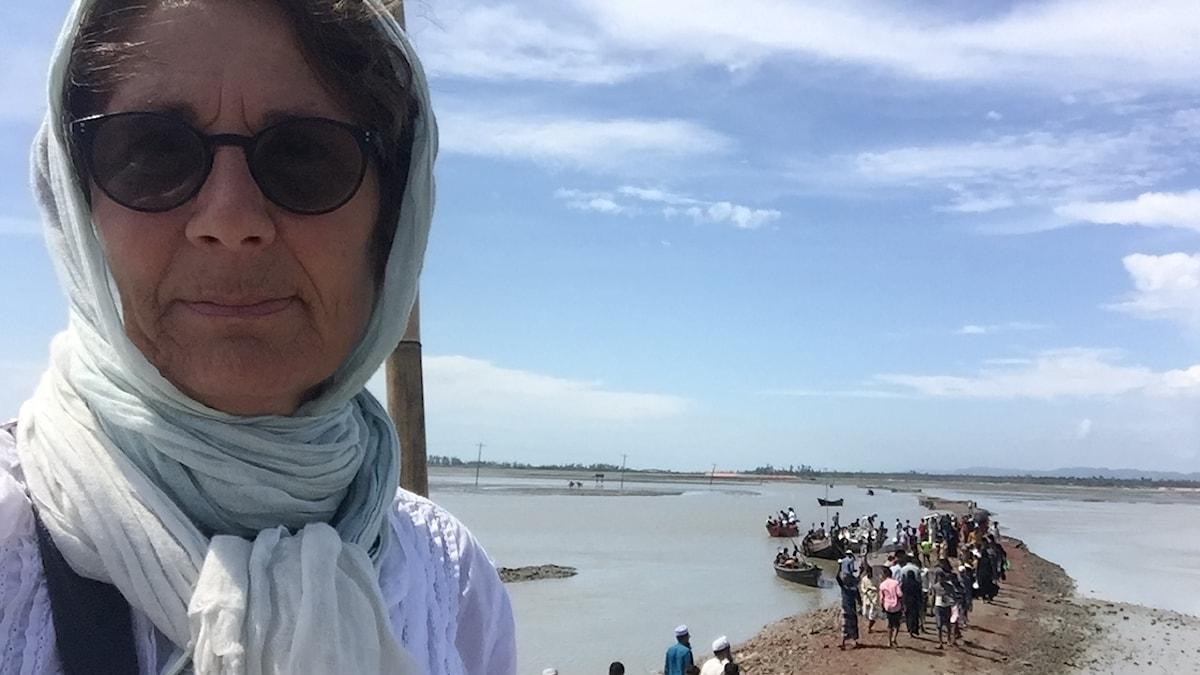 Alice Petrén med solglasögon, i bakgrunden flyktingar på en strandremsa.