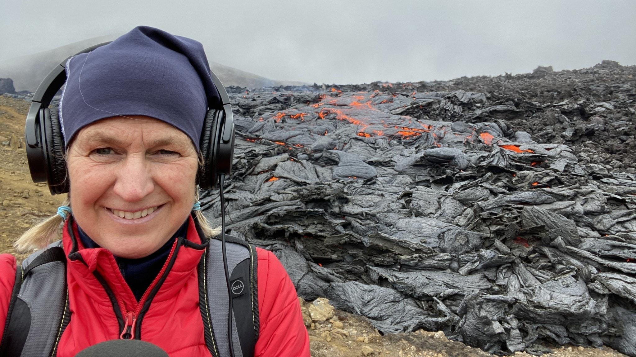 Carina Holmberg framför en rykande vulkan i Island.