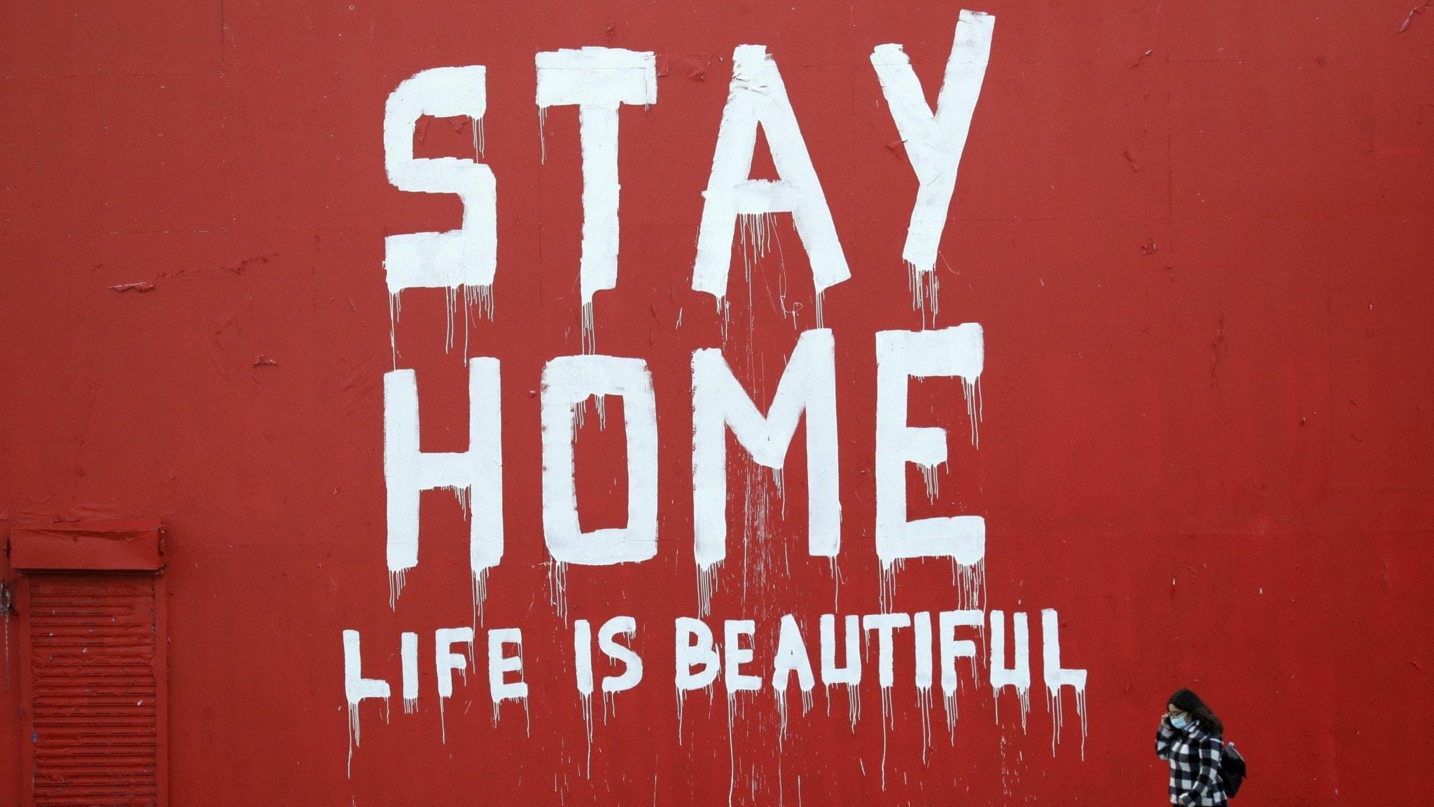 """Väggmålning i Kalifornien där det står """"stanna hemma""""."""