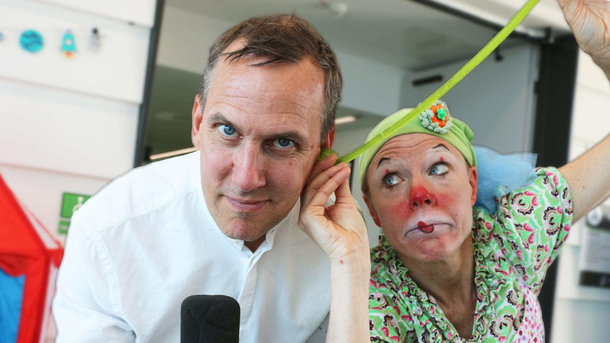Programledare: Johan Bergendorff tillsammans med sin sidekick: sjukhusclownen Tuta (Karin Bergstrand). Clownen Tuta låtsas dra ut en grön godislarv ur örat på Johan.