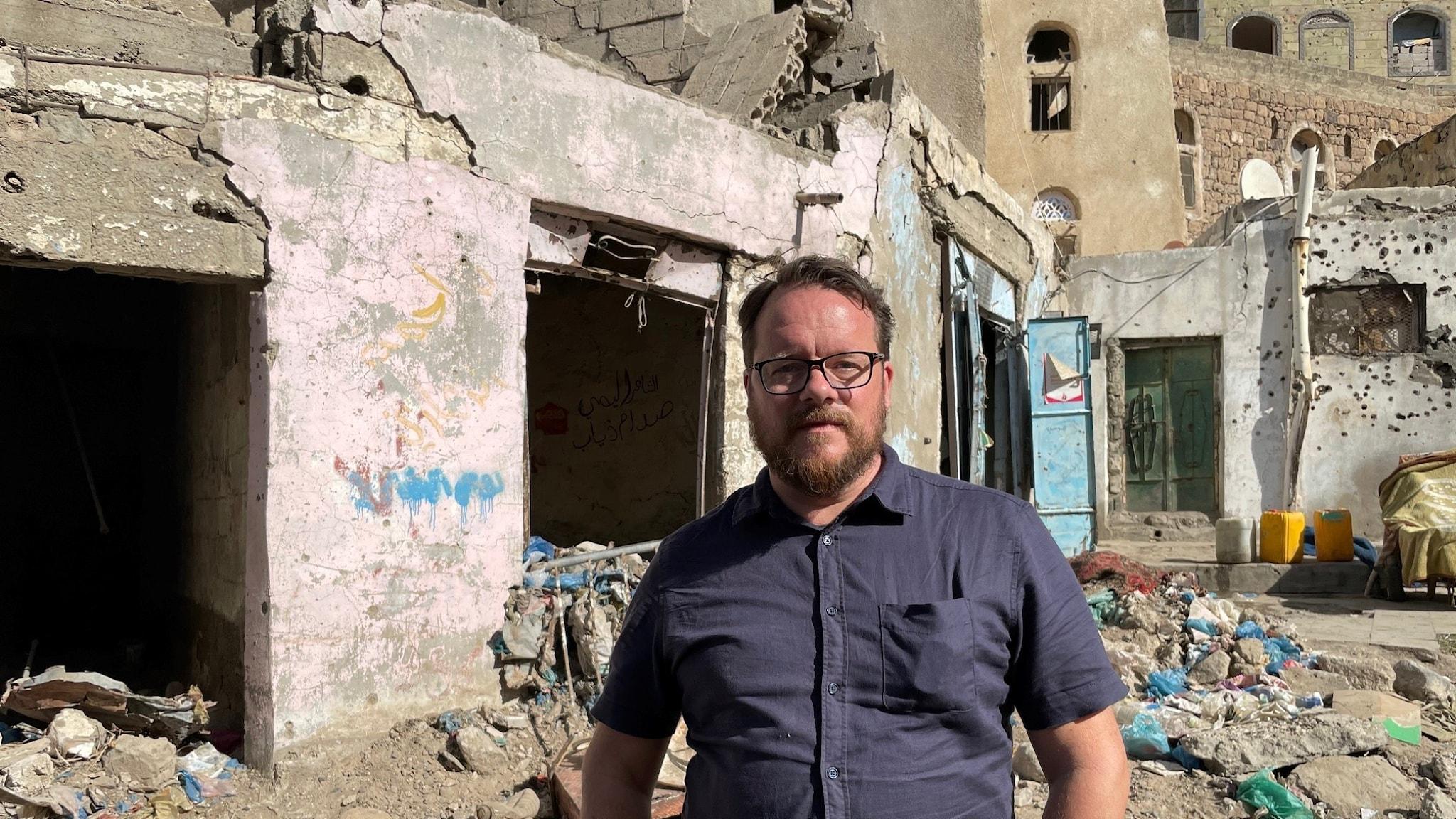 Johan-Mathias Sommarström framför husruiner i Jemen