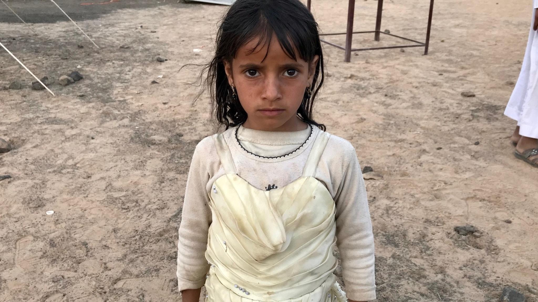 Flyktingflickan med sin klänning.