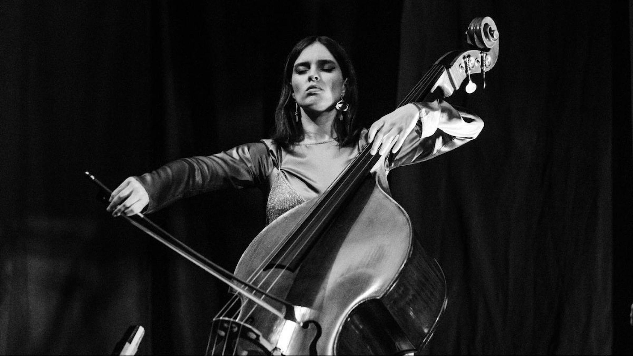 Bára Gisladóttir i svartvitt foto sitter ner och spelar på sin kontrabas.
