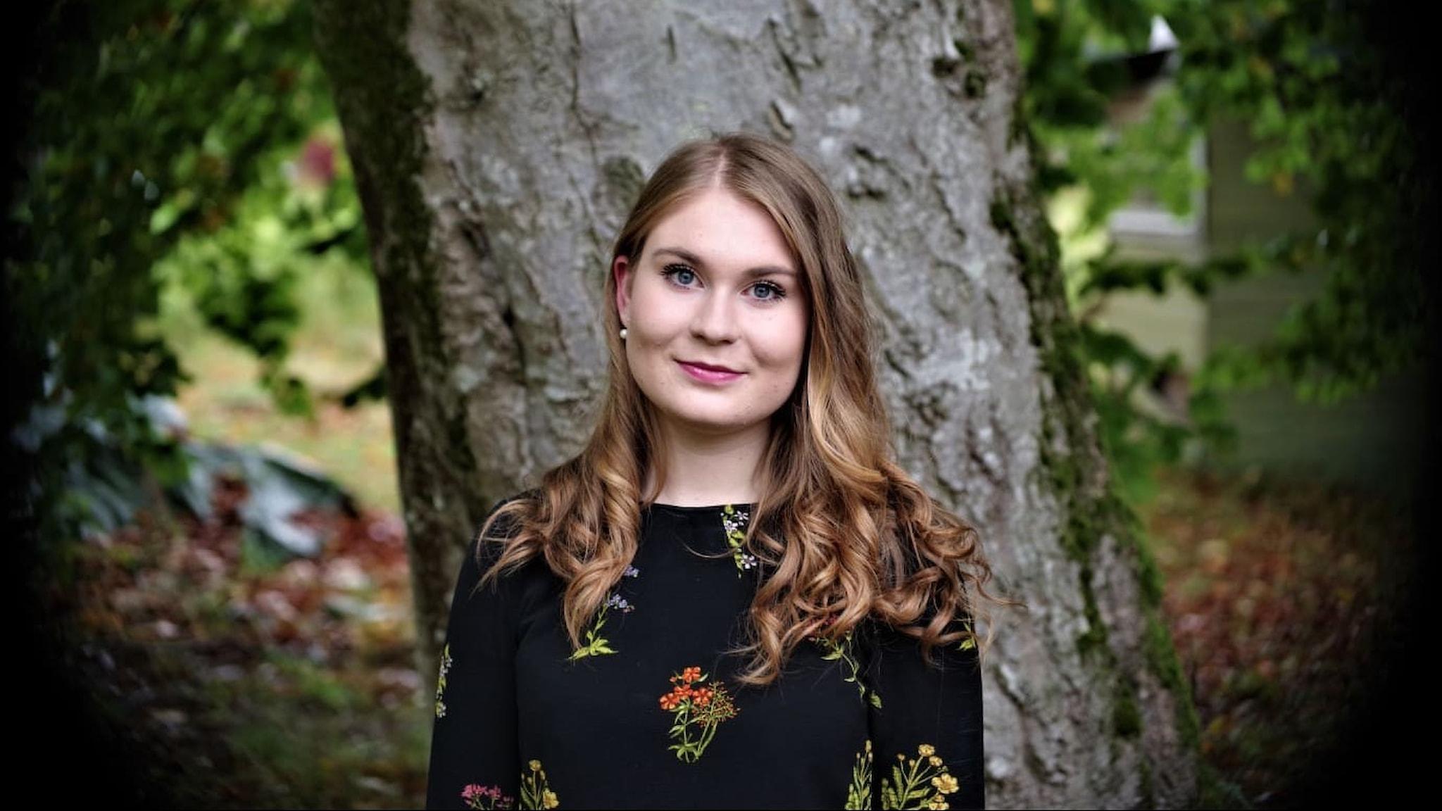 23-åriga sopranen Karolina Bengtsson i en färgbild. Hon står framför ett stort träd ser på oss med ett fint leende.