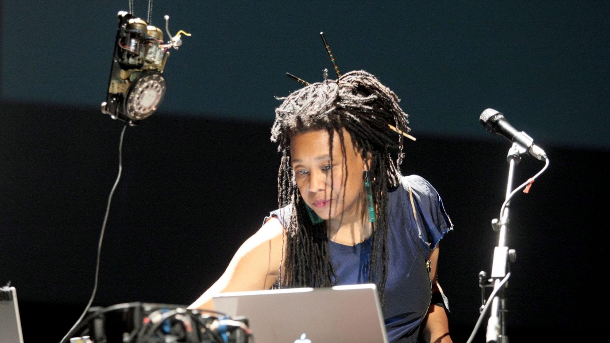 Artisten står på en scen med mikrofon och elektroniska objekt.