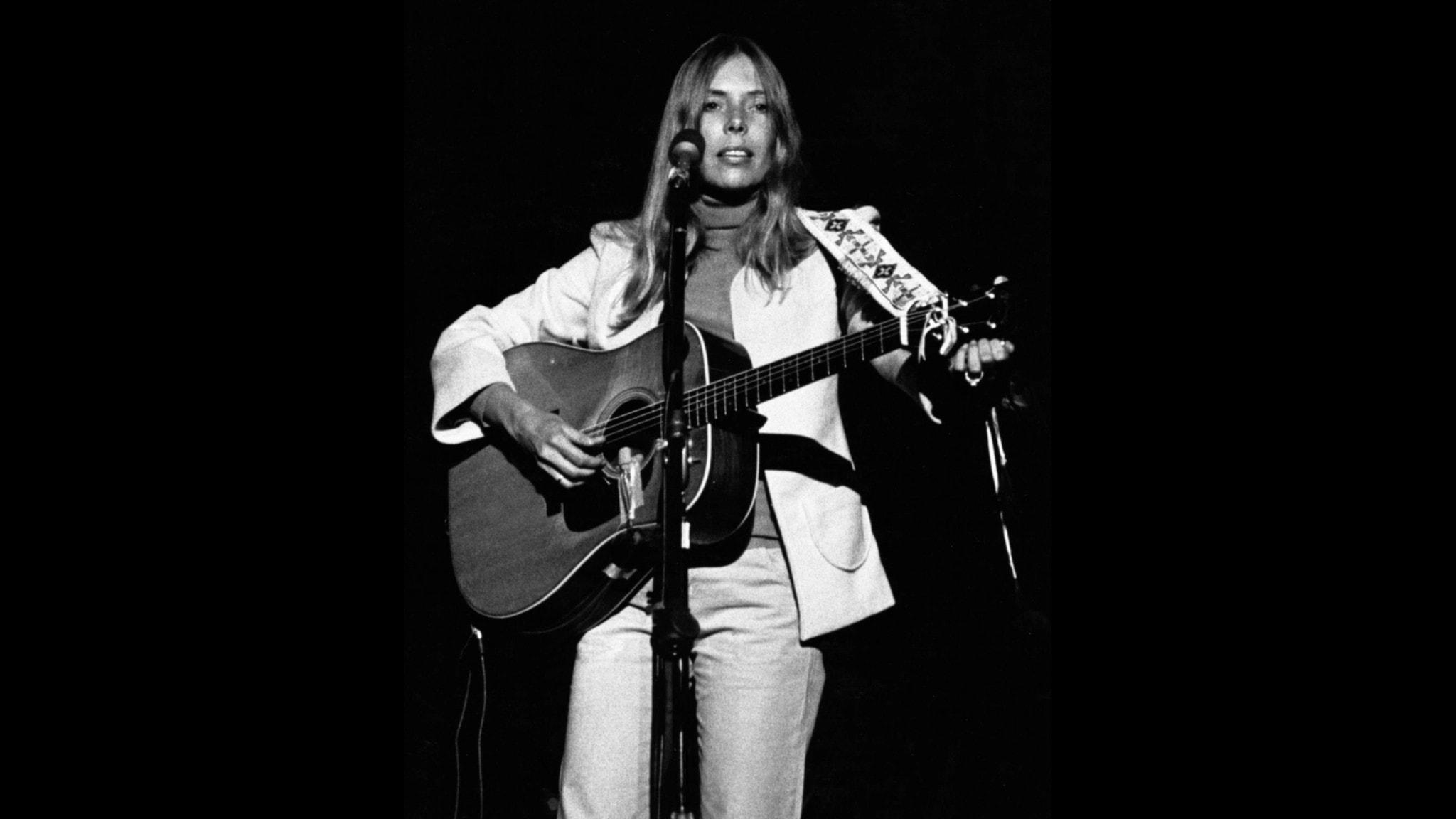 Artisten Joni Mitchell i en akustisk konsert 1974. Hon står på en scen, har långt hängande hår, har vita kläder och bär en akustisk gitarr i ett vackert brett broderat band om ryggen. Hon stämmer en av strängarna.