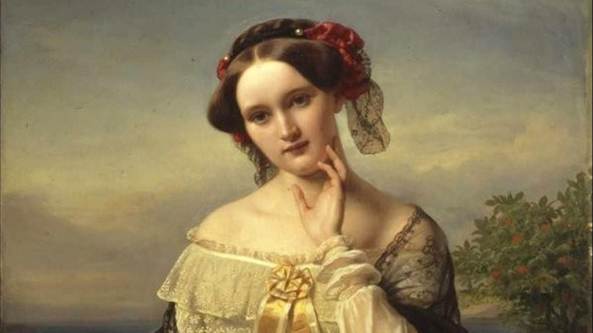 En målning i naturen av poeten och kulturkvinnan Mathilde Wesendonck av Karl Ferdinand Sohn,1850. Wikimedia Commons. Mathilde i en halvbild i färg. Uppsatt hår i en fläta med ett vinrött band. Gulvit klänning med rosettband vid barmen.