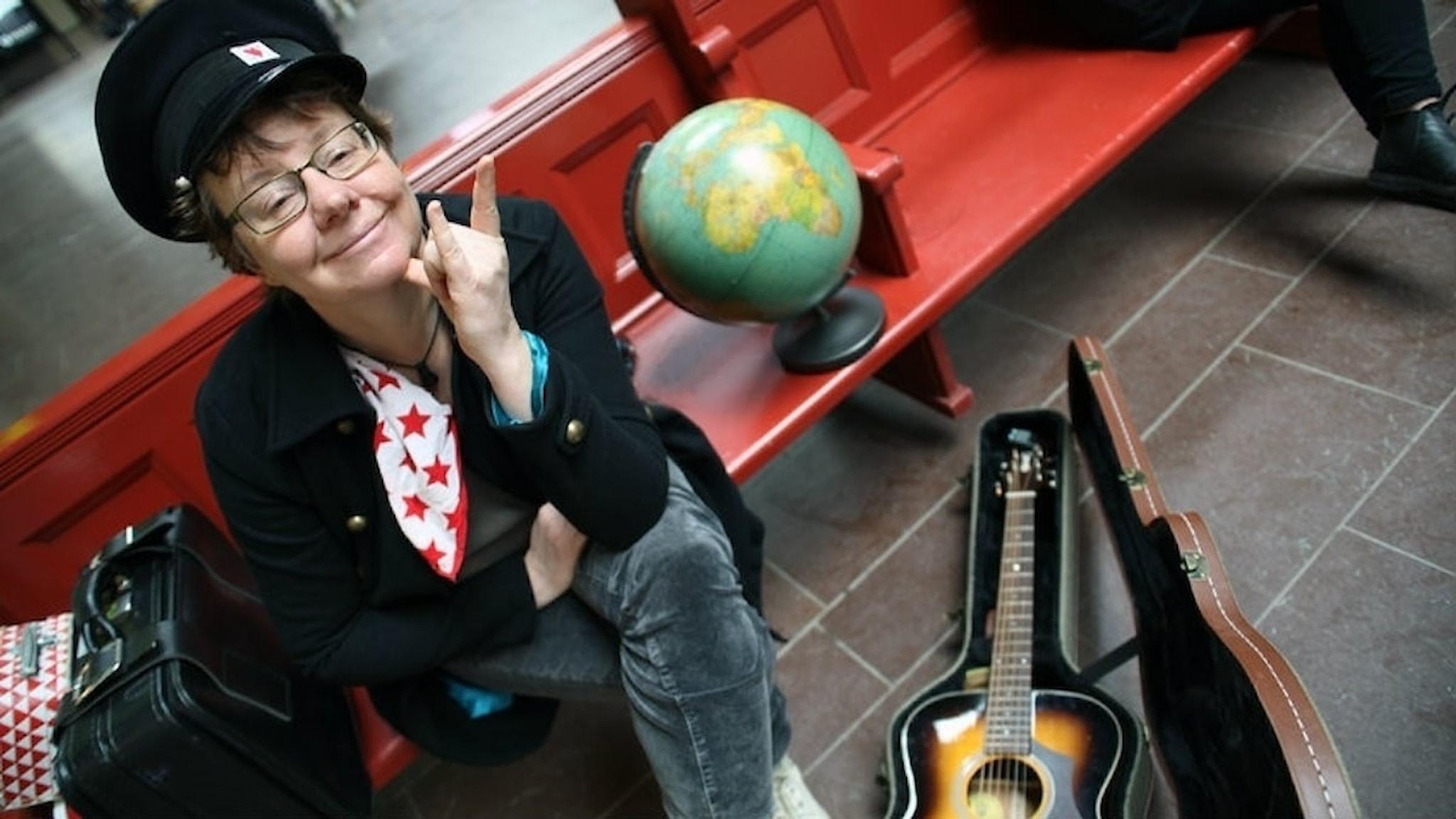 Visartisten och författaren Christina Kjellsson sitter på en röd bänk på Centralen i Göteborg. Hon bär en stinsmössa, har en jordglob bredvid sig, en akustisk gitarr i ett fodral på golvet och en svart resväska bredvid.