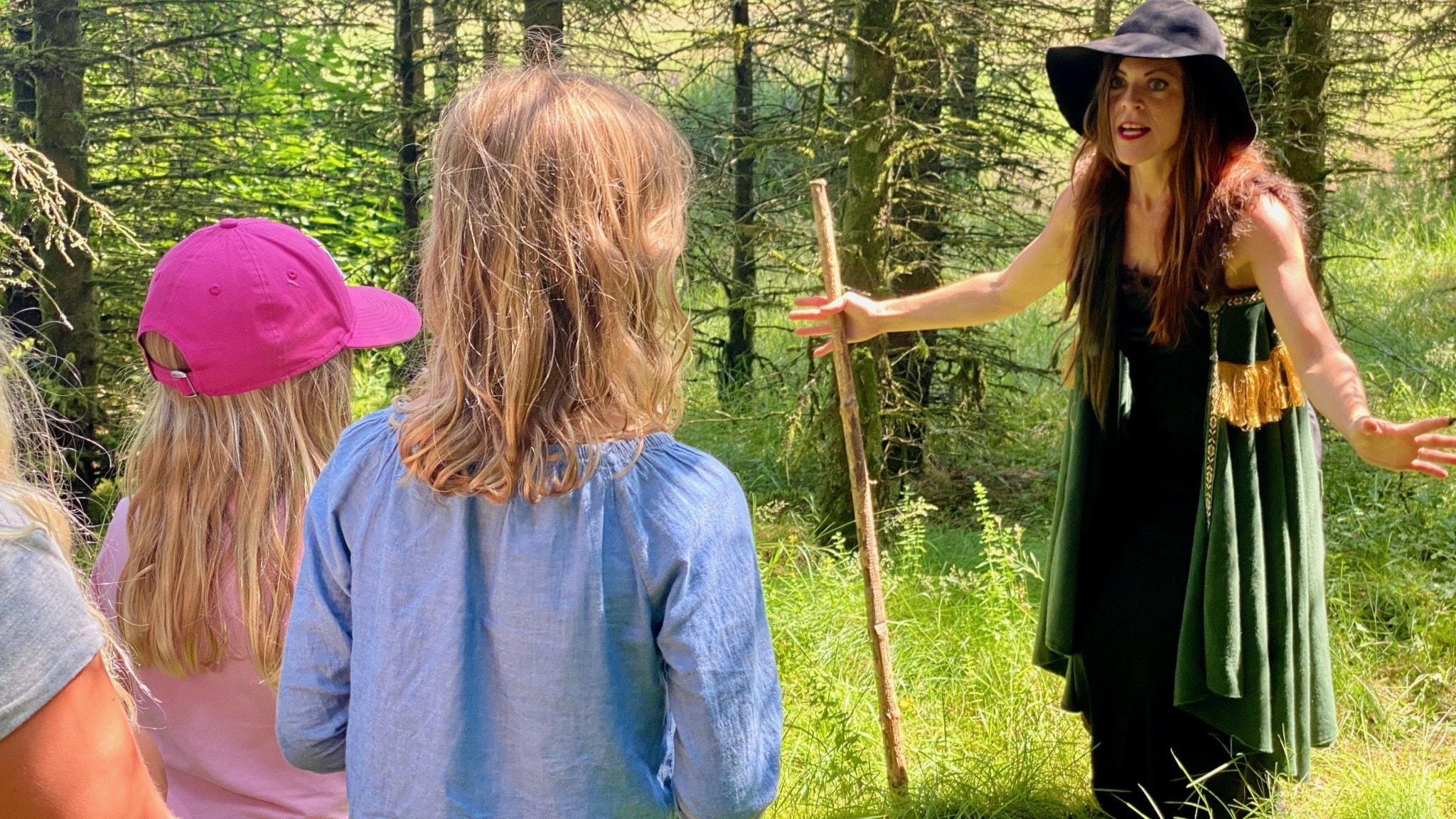 LinaMaria Bengtsson utklädd till skogsrået, i skogen framför en grupp fascinerade barn