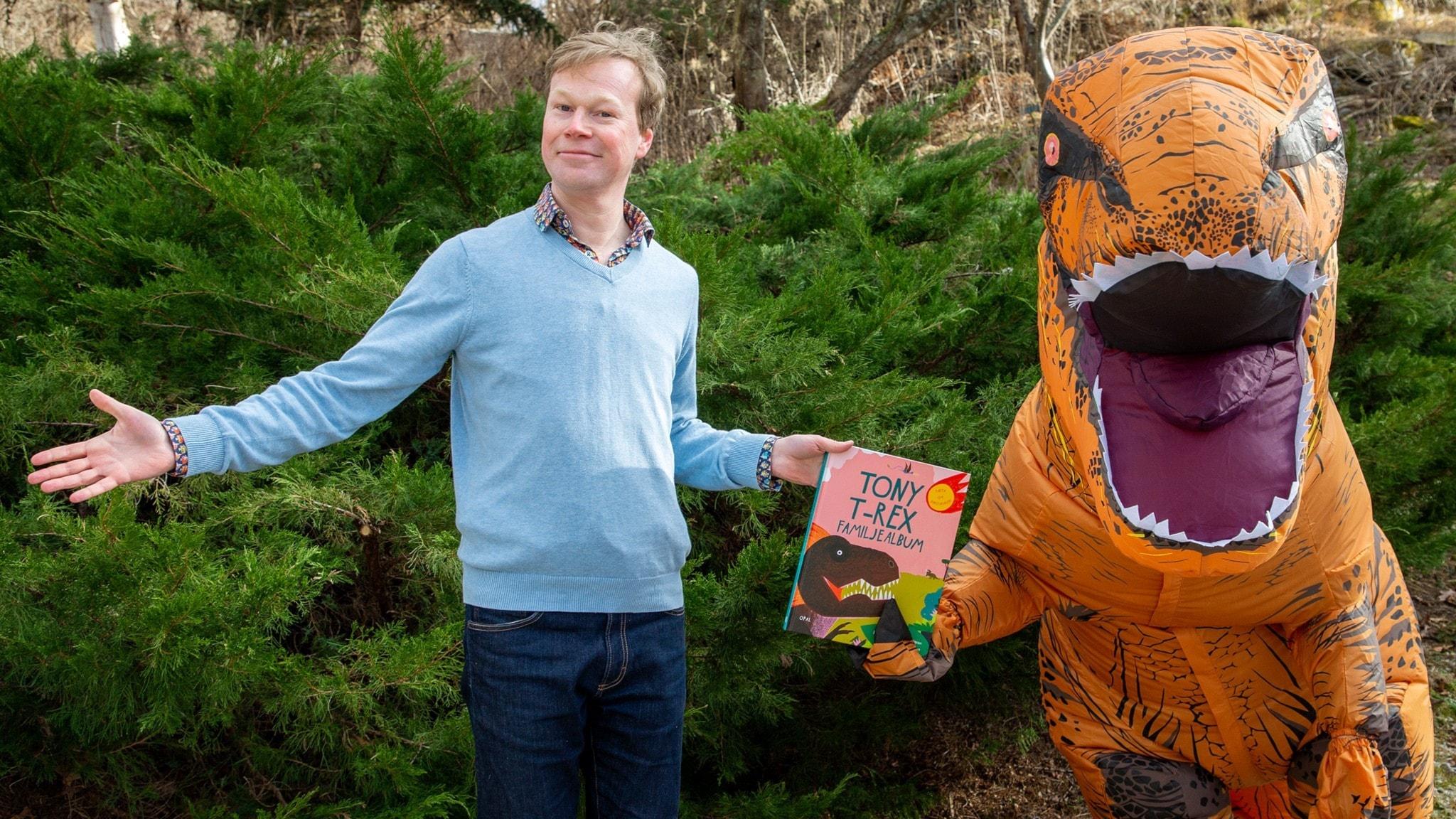 Johan Glans och en Tyrannosaurus Rex håller i boken Tony T-Rex familjealbum. Foto: Martina Holmberg