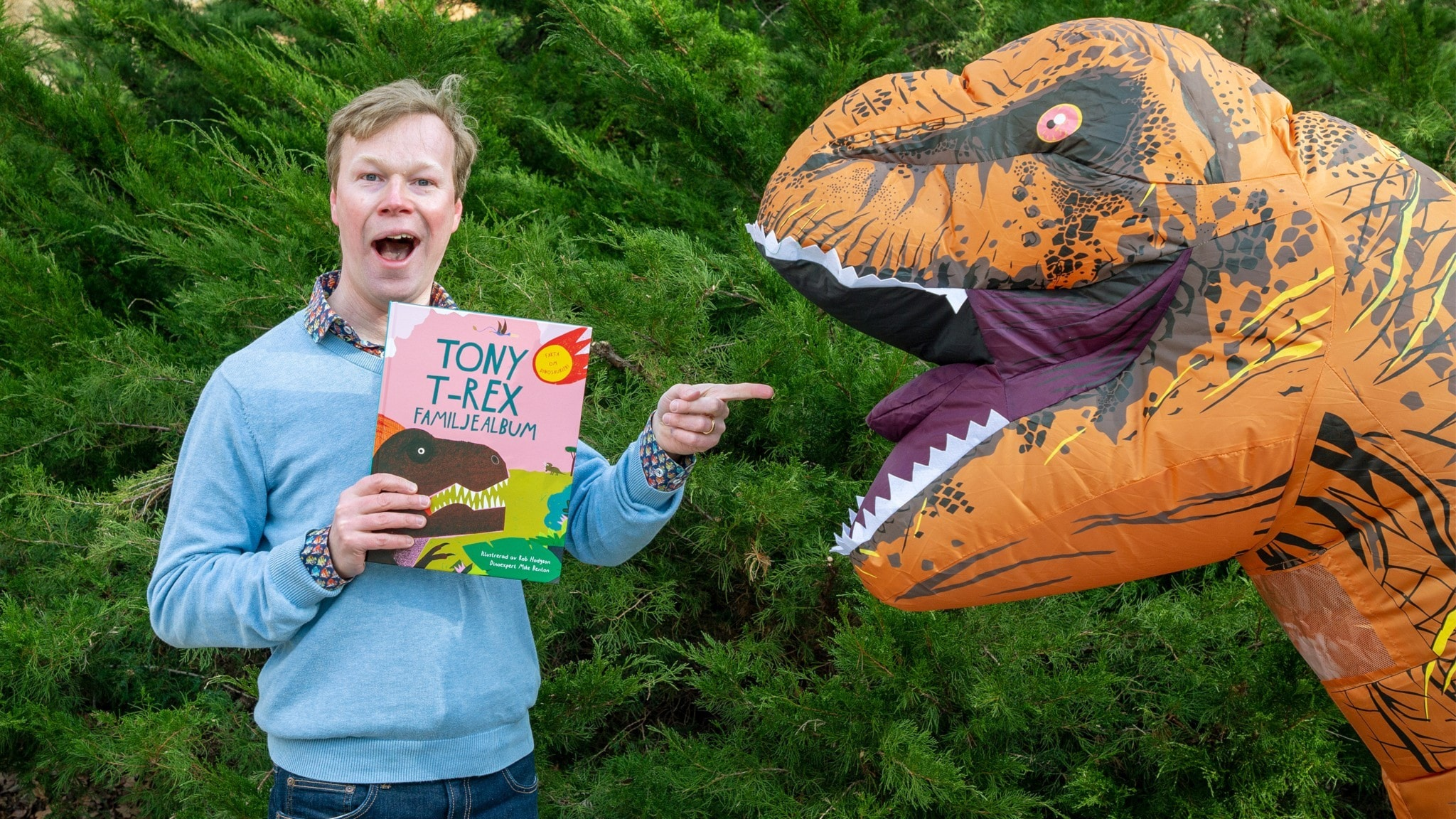 Johan Glans pekar på en Tyrannosaurus Rex och håller i boken Tony T-Rex familjealbum. Foto: Martina Holmberg
