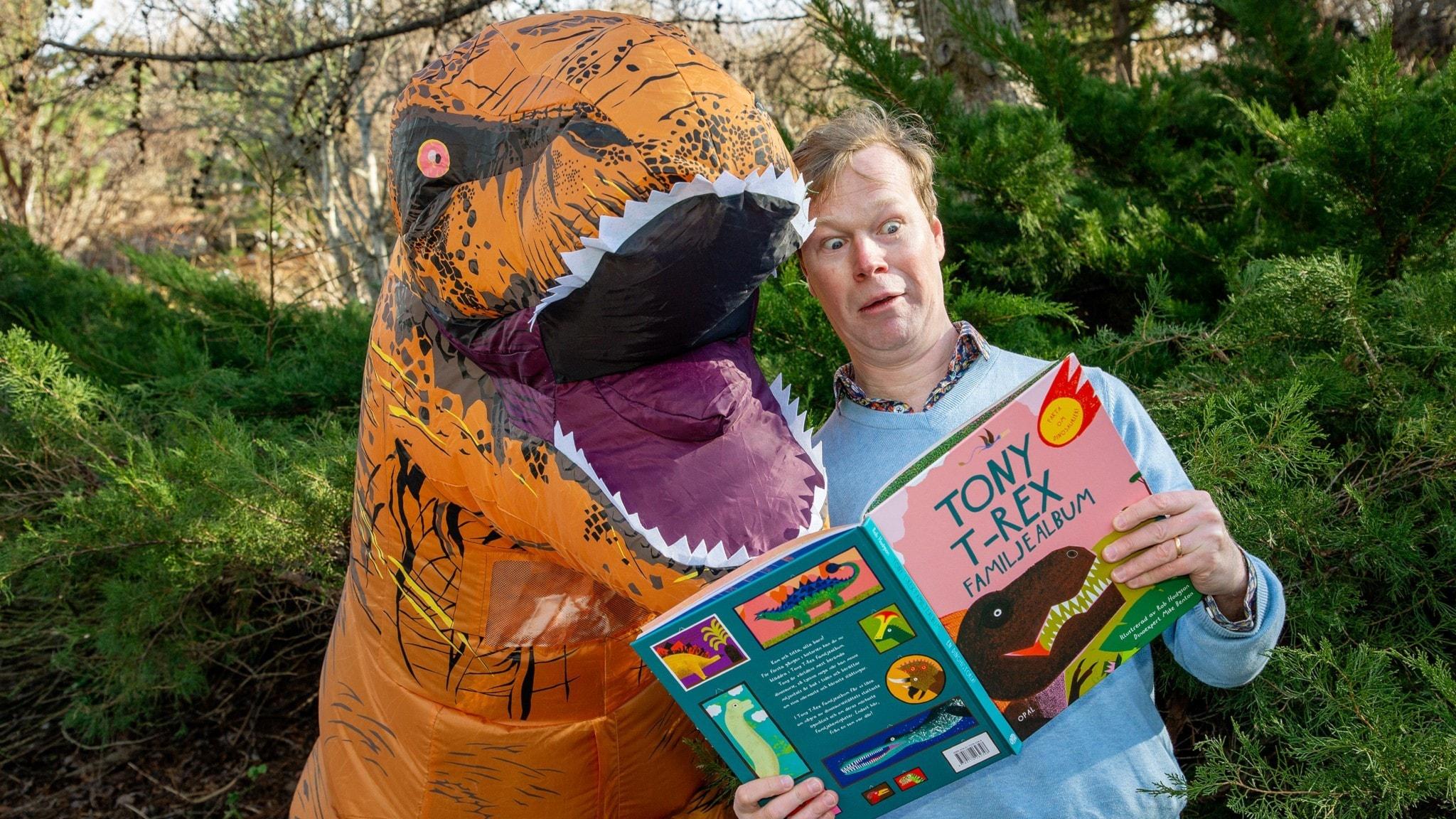 Johan Glans och Tony T-Rex läser i en dinosauriebok. Foto: Martina Holmberg