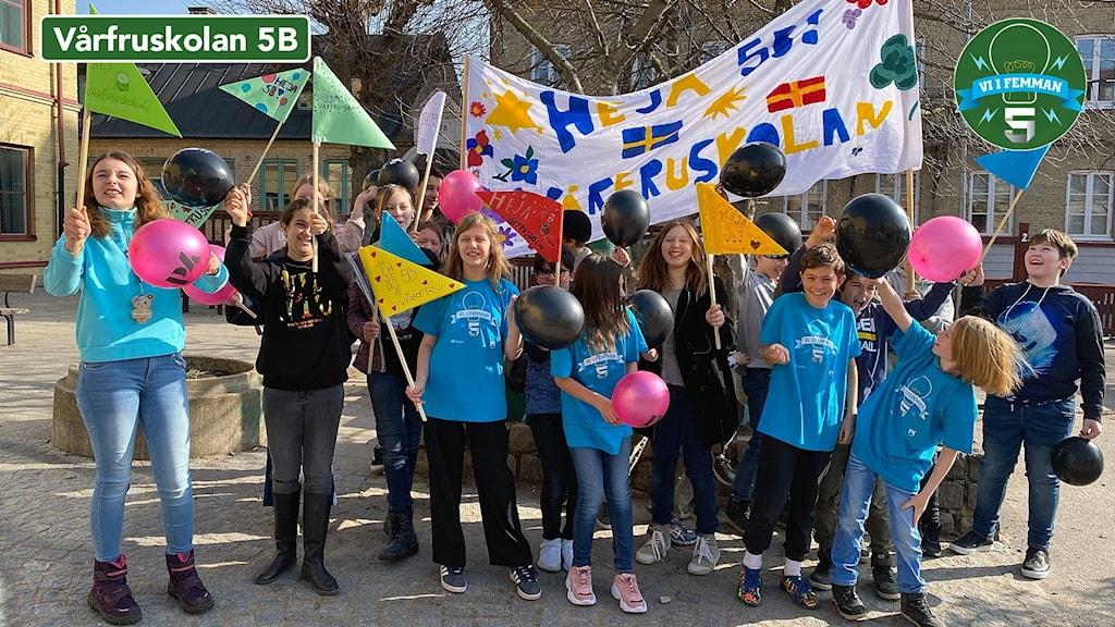 Vårfruskolans klass 5B står uppställda för fotografering. De har målat en banderoll med skolans namn på. Det är också flaggor och ballonger på bilden.